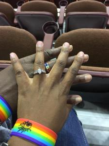 Holding hands with rings and rainbow wristbands